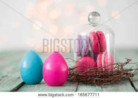 Colorful Macaroon In Nest With Toy Rabbit On Wooden Background. Easter Concept