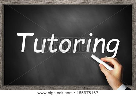businessmans hand writing tutoring on black chalkboard