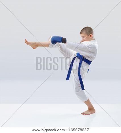 Blow leg forward beats athlete in karategi on the light background
