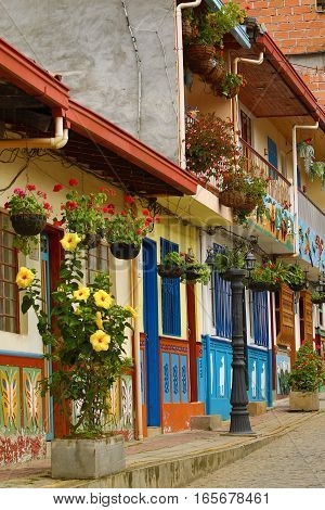 November 8, 2016 Guatape, Colombia: colourful colonial style houses lining the cobblestone street in the popular tourist town