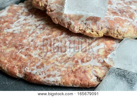 Frozen Hamburger Patties with ice cubes on stone background