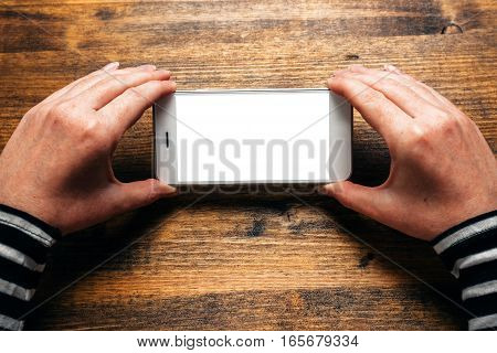 Woman using smart phone in horizontal landscape orientation for streaming movies or browsing picture gallery blank screen as copy space