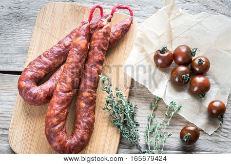 Chorizo with cherry tomatoes on the wooden board