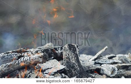 background with smoldering charred wood and red flames of fire