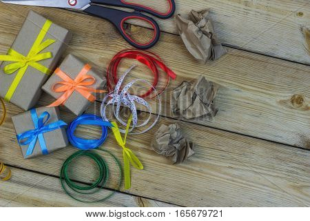 Scissors, Gift Boxes, Ribbons And Crumpled Paper On A Wooden Table