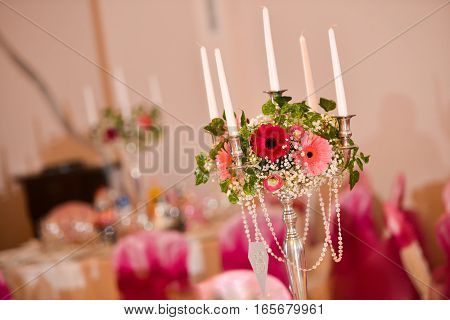 Support for candles with flowers on the table in natural light