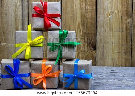 Gift Box With Paper Wrapper With Colored Ribbons, Stacked Pyramid On A Wooden Table