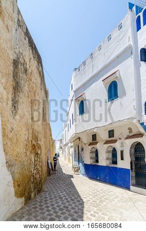 Stone alley with historic city wall and white and blue washed buildings in Asilah, Morocco, North Africa.