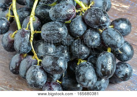 A bunch of dark grapes on a brown background.