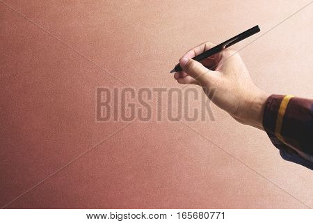 Hipster hand holding pen over old vintage wall background with copy space