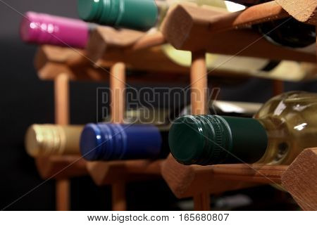 Close Up Of Green Screw Top Wine Bottle With Other Bottles In A Wooden Wine Rack