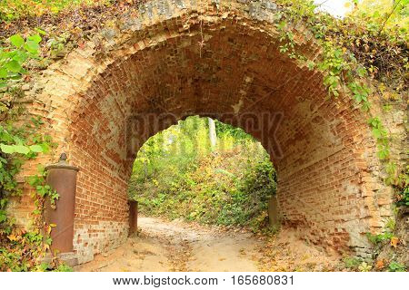 sandy road under historical arch from red bricks in Kachanivka park