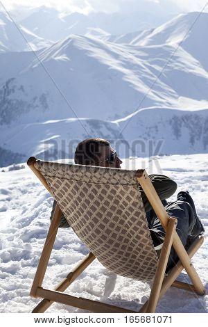 Skier at winter mountains resting on sun-lounger at nice sun day. Caucasus Mountains Georgia region Gudauri.