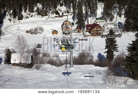 Skiers on chair-lift at ski resort in sun winter day. Caucasus Mountains. Hatsvali Svaneti region of Georgia.