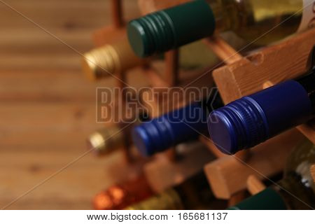Close Up Of Blue Screw Top Wine Bottle With Other Bottles In A Wooden Wine Rack