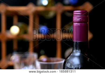 Closeup Of Burgundy Screw Top Wine Bottle With Wine Rack And Wine Glass In Out Of Focus Background