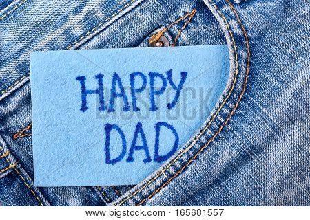 Dad's card in jeans pocket. Greeting paper on denim. Congratulation for favourite daddy.