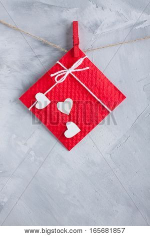 Red Gift Card Wih Paper Hearts On Gray Concrete Background.