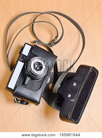 Old film camera with a fixed lens in a leather case on wooden background