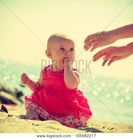 Babby Siting On Sand Looking At Hands