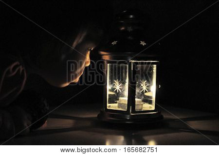 Little girl looking at candle light in lantern high iso shootcandle light in black background with soft fire