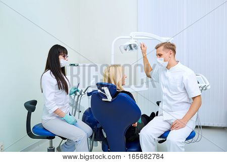 The patient, dentist and assistant in office of a dental clinic.