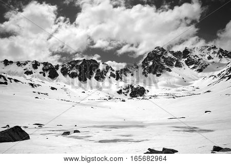 Black And White View On Frozen Mountain Lake Covered With Snow