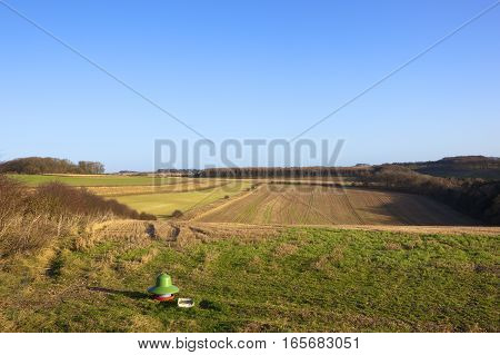 an agricultural shooting and hunting yorkshire wolds landscape with woods and hedgerows straw stubble and a pheasant feeder under a clear blue sky in winter
