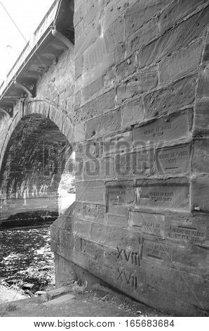 A stone bridge over the river Tay in Perth showing various water levels over the years