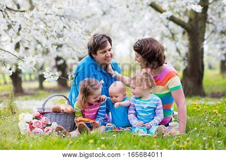 Family With Children Enjoying Picnic In Spring Park
