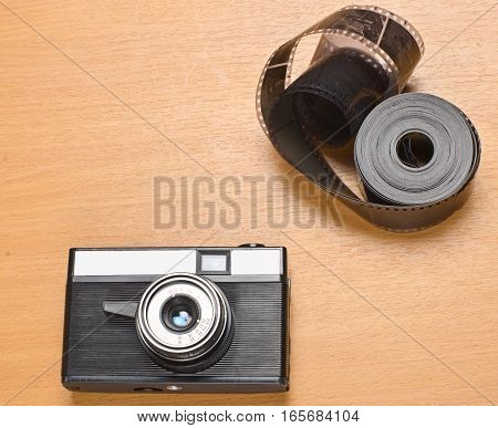 Old film camera with lens a large roll of film lying on a wooden surface