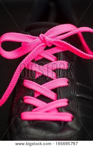 pink lacing on man sport black sneaker