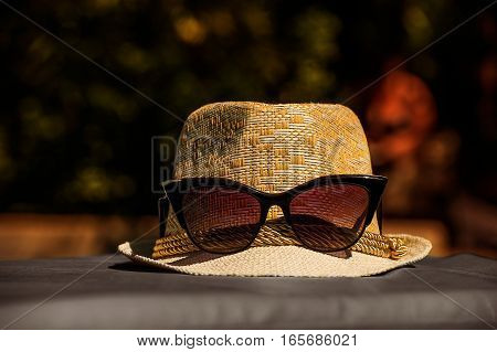 The bright sunny picture backgroundtexture of the straw white hat with red glasses spectacles on the on the gray floor in warm tones with green and orange bokeh