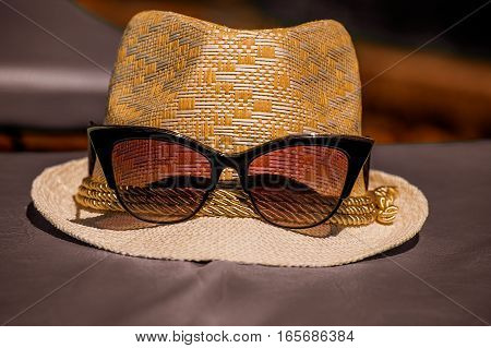 The bright sunny picture backgroundtexture of the straw white hat with red glasses spectacles on the on the gray floor in warm tones with shadow on the hat