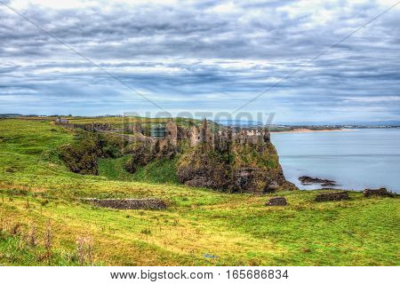 Ancient castle built on a rock surrounded by sea. Tone mapped high definition range photo of an old castle rise on a hight cliff rock surrounded by deep water with a beautiful cloudy skyline and emerald glen.