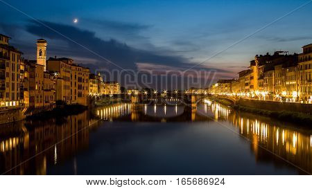 Night scene with a beautiful skyline with a moon. Lights reflect on a soft tranquil waters of a river. Residential view on both sides of the river embankments. Bridge, reflected on the water is the center if the photo.