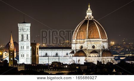 Night scenic view on the most famous italian cathedral located in Florence - Cupola del Brunelleschi. Illuminated cathedral surrounded by silhouettes of houses in front of a dark sky.