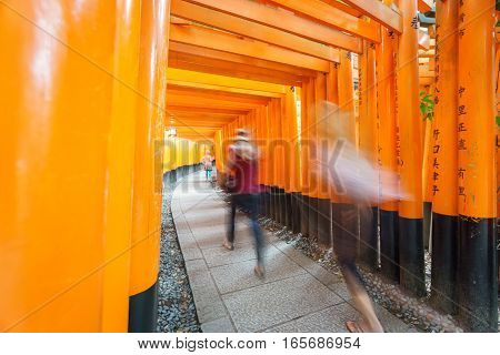 Wide angle view of Torii gates in Fushimi Inari Shrine with blurred tourists in Kyoto, Japan