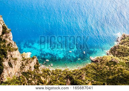 Top down view on a blue clean turquoise lagoon with a boat. Clear view from the above on a tranquil blue lagoon. Lonely motor boat is floating on a blue lagoon waters. High cliffs surround lagoon from the ocean. poster