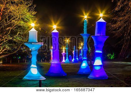 Long perspective of artificial lighten colored candles at night. Light show at night, artificial man-size candles are lighten up in a garden