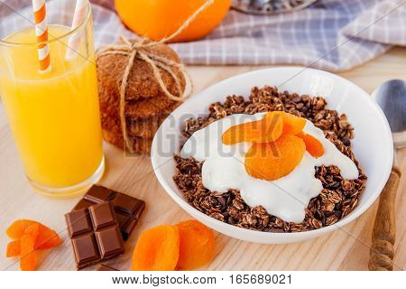 Chocolate Granola With Dried Apricots And Yogurt In The White Bowl. Glass Of Fresh Orange Juice.