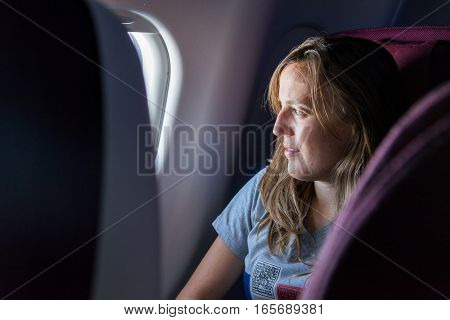 Attractive young brunette looking through airplane window. Day dreaming during flight.