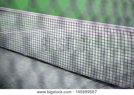 Exterior tennis paddle court. White net in diagonal composition.