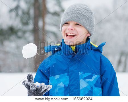 Happy teen boy smiling outdoors play in snow on cold winter day. Child enjoying in snowy park. Outdoor fun for childhood Christmas vacation.
