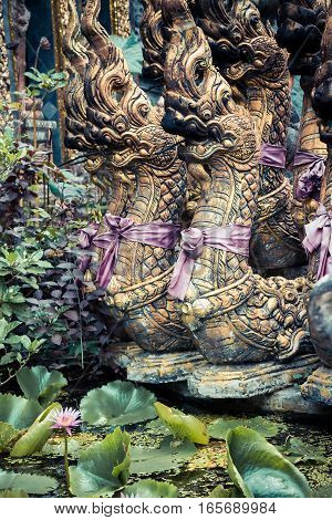 Sculptures of Buddhism deities in Asian style tropical garden