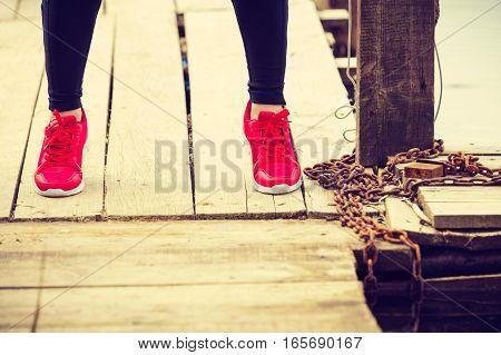 Slim Fit Legs Wearing Red Sport Shoes On Wooden Pier
