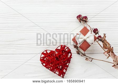 Stylish Red Present And Heart And Roses On White Rustic Wooden Background. Happy Valentine Day Card
