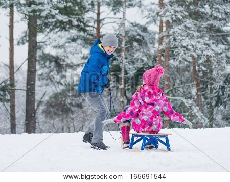 Happy boy and girl riding sled and having fun. Children play outdoors in snow - sledding. Kids sled in snowy park in winter. Outdoor fun for family Christmas vacation.