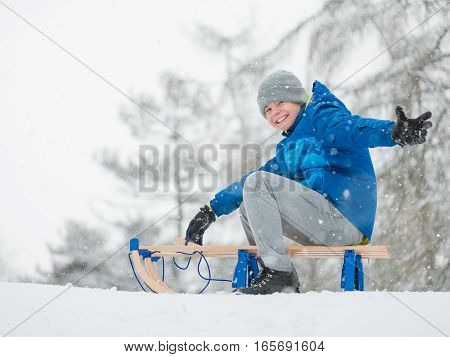 Happy boy riding sled and having fun. Child play outdoors in snow - sledding. Kid sled in snowy park in winter. Outdoor fun for childhood Christmas vacation.