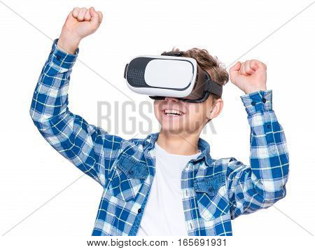 Happy teen boy wearing virtual reality goggles watching movies or playing video games, isolated on white. Cheerful smiling teenager looking in VR glasses. Funny child experiencing 3D gadget technology.
